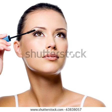 Beautiful woman applying mascara on her eyelashes - isolated on white - stock photo