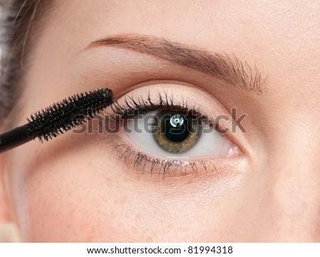 Beautiful woman applying mascara on her eyelashes - isolated on white - stock photo