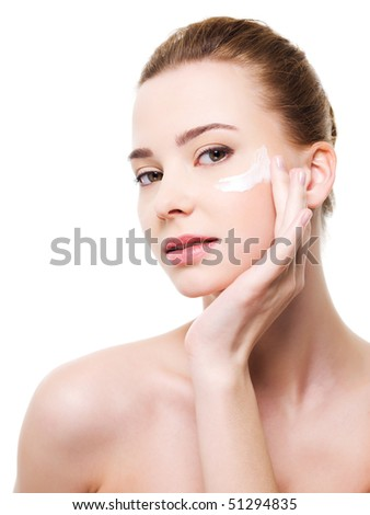 Beautiful woman applying moisturizer cosmetic under eyes - on a white