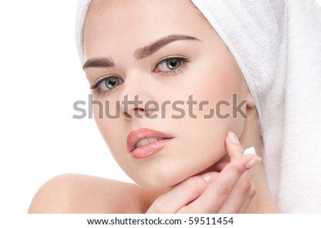 Beautiful woman applying moisturizer cream on face. Close-up fresh young woman face isolated on white - stock photo