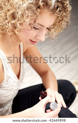 Beautiful Woman applying nail polish - stock photo