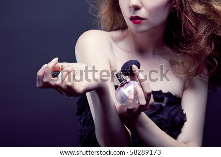 beautiful woman applying perfume on her body - stock photo