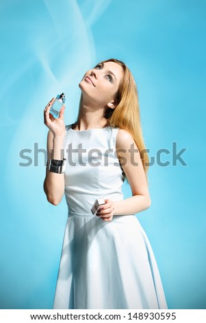Beautiful woman applying perfume on her body over white - stock photo