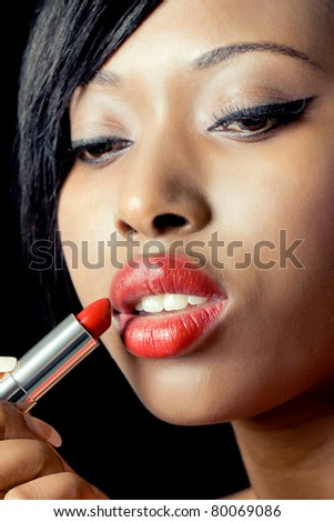 Beautiful woman applying red lipstick, closeup shot - stock photo