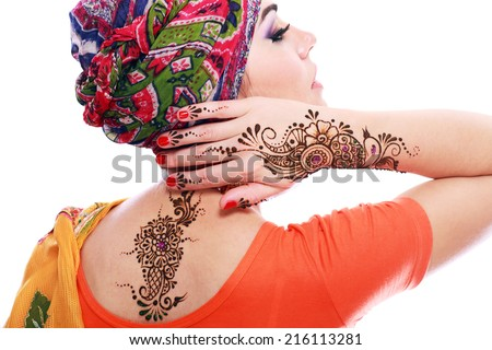 Beautiful woman arabian make up and turban on head with detail of henna being applied to hand and backt isolated  - stock photo