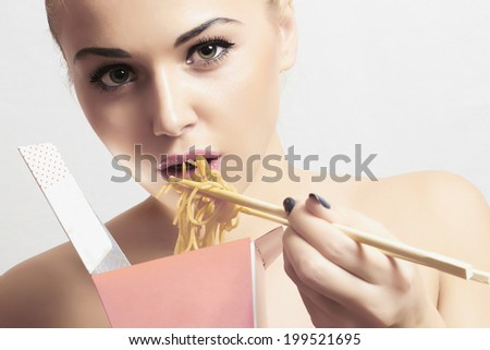 Beautiful woman are eating noodles.Chinese sticks. fast food.food delivery. pink. delicious. enjoy meal - stock photo