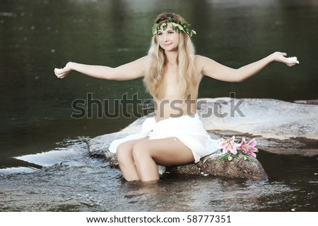 Beautiful woman as a forest nymph on the river - stock photo
