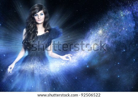Beautiful woman as galaxy godness holding a milky way on blue background - stock photo