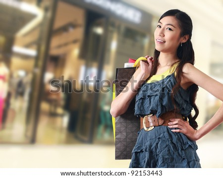 Beautiful woman at a shopping center with bags and smiling - stock photo
