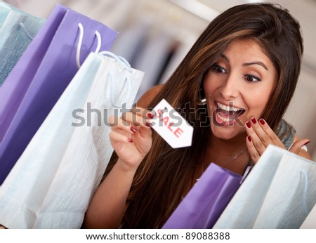 Beautiful woman at an exciting shopping sale - stock photo