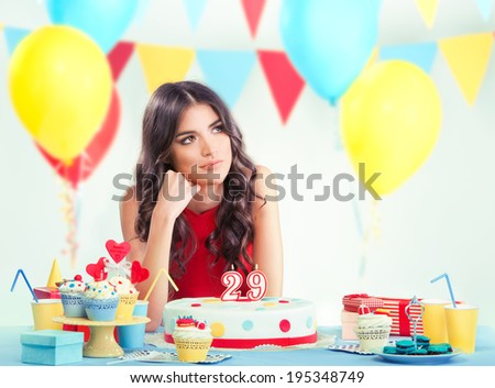 Beautiful woman at her birthday party thinking  - stock photo