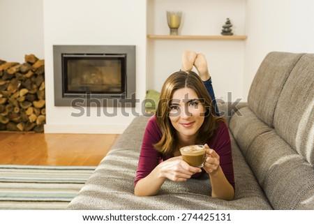 Beautiful woman at home drinking a capuchino - stock photo