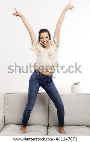 Beautiful woman at home listening music and dancing over the couch
