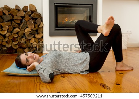 Beautiful woman at home lying on the floor - stock photo