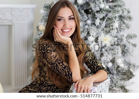 Beautiful woman at home over christmas tree
