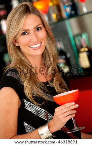 Beautiful woman at the bar drinking a cocktail - stock photo
