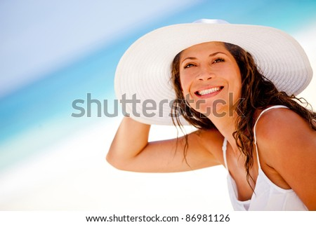 Beautiful woman at the beach wearing a hat and smiling - stock photo