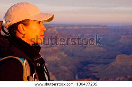 Beautiful woman at the Grand Canyon looking enjoying sunset - stock photo