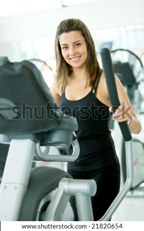 beautiful woman at the gym exercising in the cardio machines - stock photo