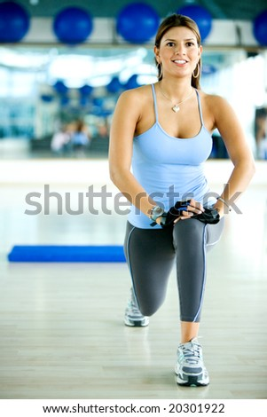 beautiful woman at the gym smiling doing stretching exercises - stock photo