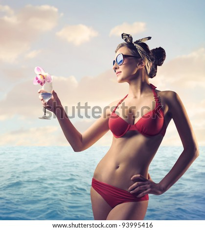 Beautiful woman at the seaside holding a drink - stock photo