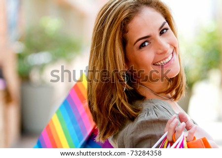 Beautiful woman at the shopping center holding bags - stock photo