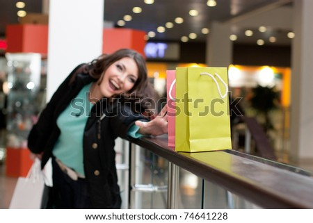 Beautiful woman at the shopping center with bags - stock photo