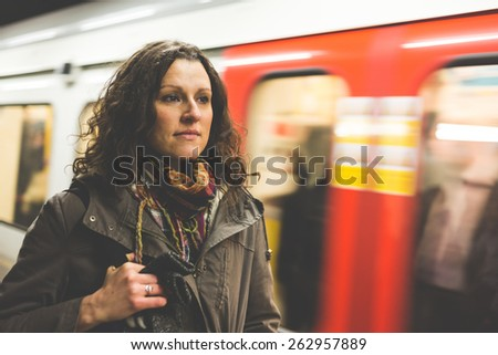 Beautiful woman at tube station in London with blurred train passing on background. She wears winter clothes and look in front of her while waiting for the train. - stock photo