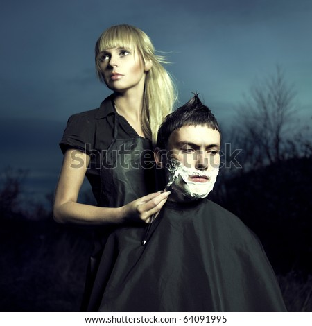 Beautiful woman barber shaves a courageous man. Surreal picture - stock photo