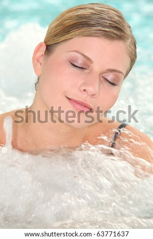 Beautiful woman bathing in jacuzzi of spa center - stock photo