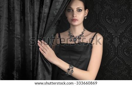 Beautiful woman behind black velvet curtain - stock photo