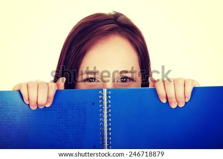 Beautiful woman behind blue workbook.  - stock photo