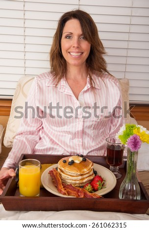 Beautiful woman being served breakfast in bed - stock photo
