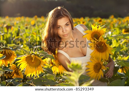 beautiful woman between sunflowers - stock photo