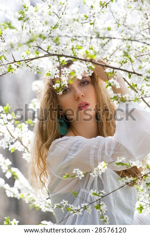 beautiful woman between tree with white flowers - stock photo