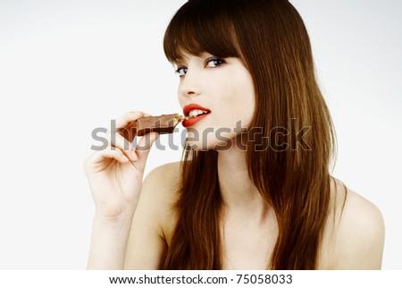 beautiful woman biting a bar of chocolate in a sexy way - stock photo