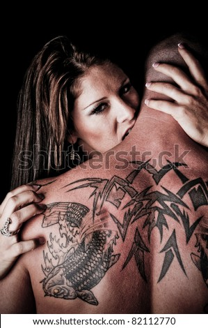 Beautiful Woman biting, hugging and looking over the shoulder of a man with tattoos - stock photo