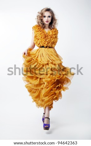 Beautiful Woman Blonde Fashion Model in Yellow Dress Isolated over White Background. Shopping Mall. Sales and Discounts Concept - stock photo