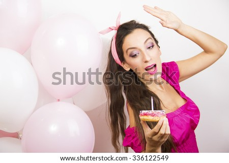 Beautiful woman blowing candle on birthday cake. - stock photo