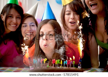 Beautiful woman blowing candles on a birthday party with her friends - stock photo