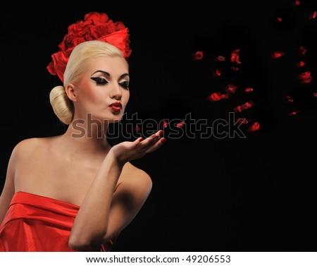 Beautiful woman blowing rose petals - stock photo