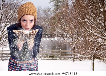 Beautiful woman blowing snow off of her hands - stock photo