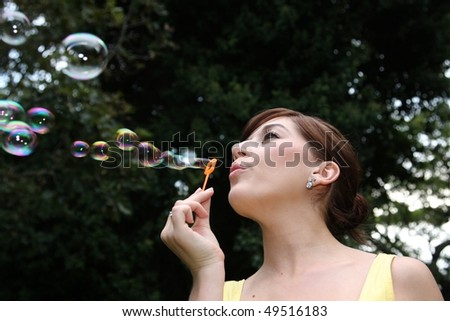 Beautiful woman blowing soap bubbles outdoors