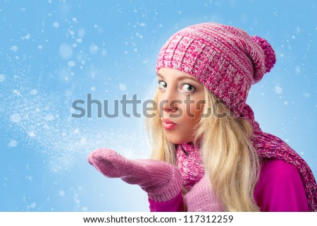 beautiful woman blowing to snowflakes over blue background and looking at camera - stock photo