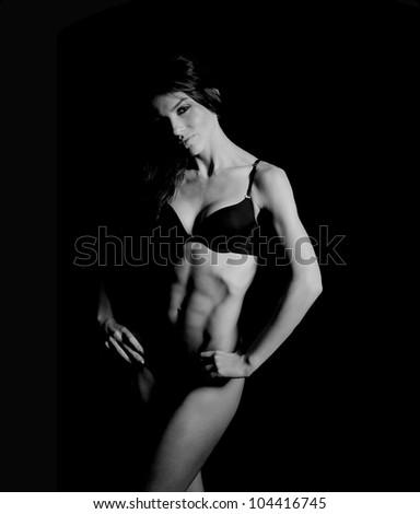 beautiful woman bodybuilder posing in black bikini on black background - stock photo