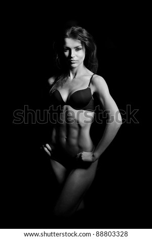 beautiful woman bodybuilder posing in black bikini on black background - stock photo