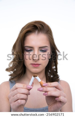 Beautiful woman breaking cigarette and no smoking concept. Focus on cigarette - stock photo