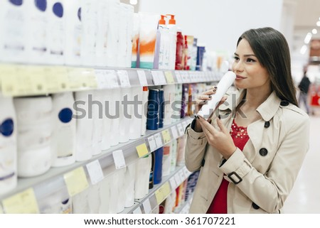 Beautiful woman buying body care products in supermarket - stock photo