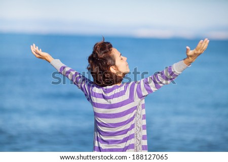 Beautiful woman by the sea with her arms outstretched - stock photo