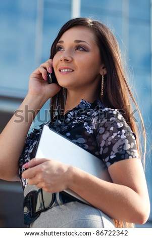 beautiful woman calling by mobile phone over blue glass building background - stock photo